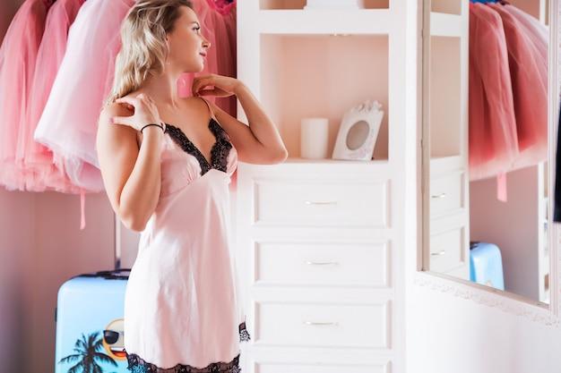 Piękna blondynka w różowej koszuli patrzy na siebie w lustrze w swojej garderobie lub sypialni.