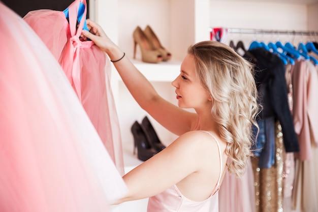 Piękna blondynka w różowej koszuli wybiera strój w swojej garderobie w domu.