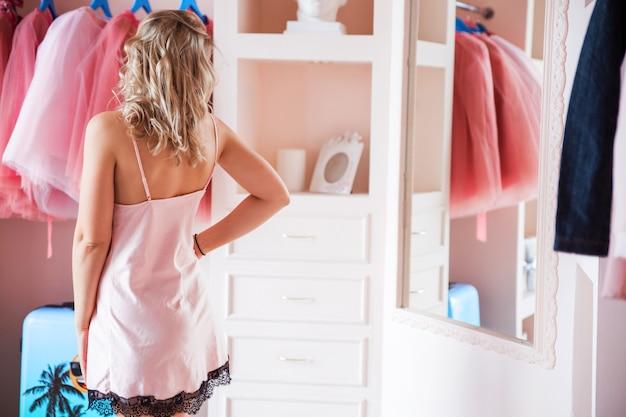 Piękna blondynka w różowej piżamie patrzy na siebie w lustrze w swojej garderobie lub sypialni. dziewczyna stoi plecami do aparatu.