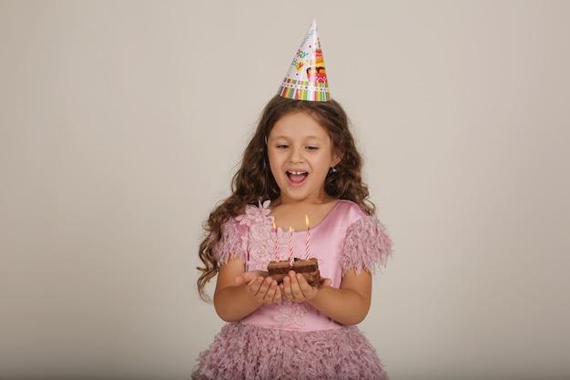 Piękna blondynka w różowej sukience z kawałkiem ciasta w dłoniach urodziny