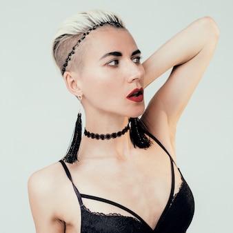 Piękna blondynka w seksownej bieliźnie i akcesoriach. choker i kolczyki trend