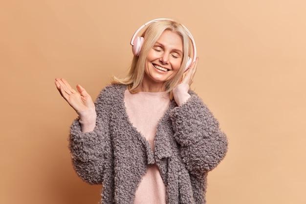 Piękna blondynka w średnim wieku zamyka oczy i nosi słuchawki stereo, słuchając przyjemnej melodii przez słuchawki ubrane w modne zimowe ubrania odizolowane na brązowej ścianie studia
