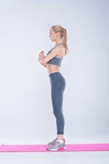 Piękna blondynka w stroju sportowym ćwiczy na macie fitness na szarym tle