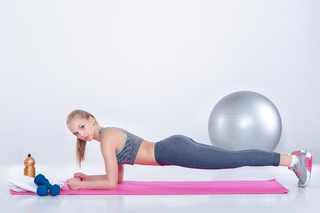 Piękna blondynka w stroju sportowym robi ćwiczenia z deski na macie fitness na szarym tle