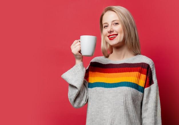 Piękna blondynka w swetrze z filiżanką kawy na czerwono