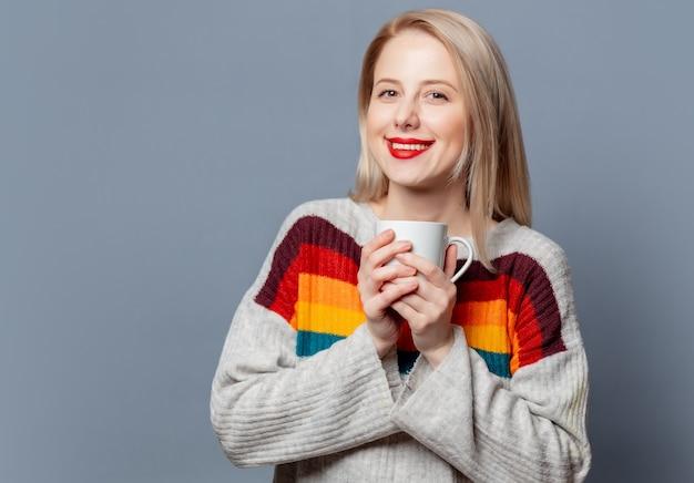Piękna blondynka w swetrze z filiżanką kawy na szaro