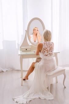 Piękna blondynka w szlafroku z białej koronki siedzi przed lustrem.