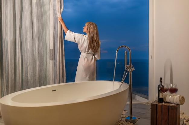 Piękna blondynka w szlafroku zasłaniająca zasłony do kąpieli