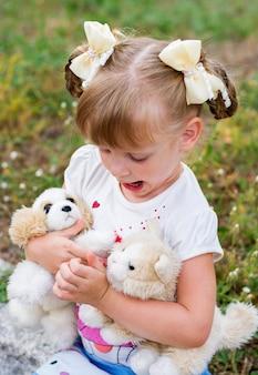 Piękna blondynka w wieku 4 lat, w lekkich ubraniach i lekkich kokardkach, przytula pluszaki i patrzy na nie emocjonalnie