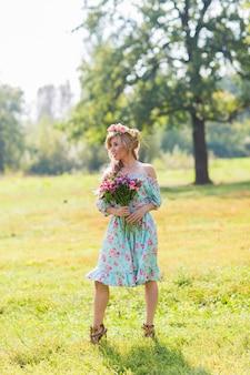 Piękna blondynka z bukietem kwiatów na wsi.