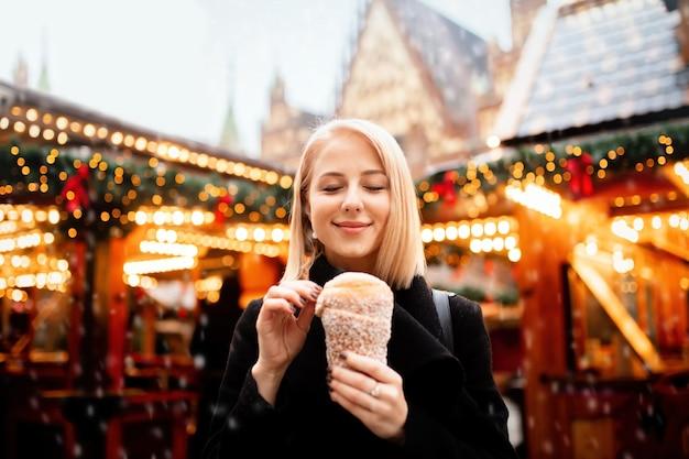 Piękna blondynka z ciastem pluć na jarmarku bożonarodzeniowym we wrocławiu