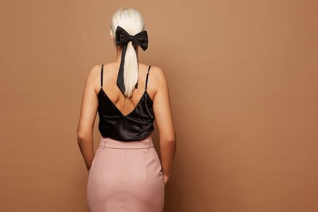 Piękna blondynka z czarną kokardą w fryzurze, ubrana w czarną bluzkę z nagimi plecami i spódniczką midi, pozuje plecami na beżowym tle, odizolowana.