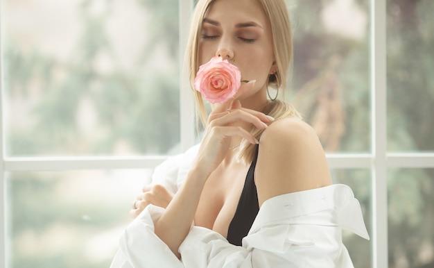 Piękna blondynka z delikatnym pączkiem róży idealna koncepcja piękna skóry skin