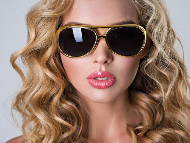 Piękna blondynka z długimi falowanymi włosami.