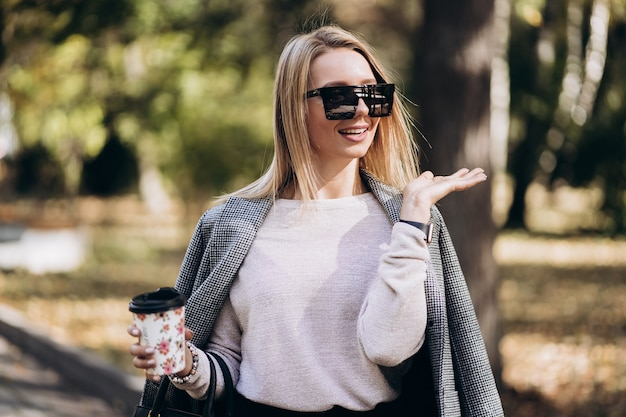 Piękna blondynka z filiżanką kawy na ulicy. portret stylowe uśmiechnięte kobiety biznesu w ciemne spodnie, kremowy sweter i okulary przeciwsłoneczne. koncepcja mody. kobiecy styl biznesowy. wysoka rozdzielczość.