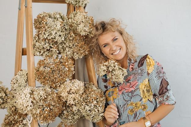 Piękna blondynka z kręconymi włosami, dekorator kwiaciarni. szczęśliwy wśród jesiennych kwiatów hortensji. zdjęcie wysokiej jakości