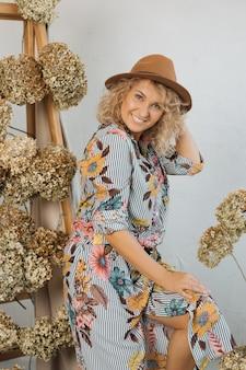 Piękna blondynka z kręconymi włosami w kapeluszu. jesienna stylizowana strefa fotograficzna wykonana z naturalnych suszonych kwiatów hortensji.