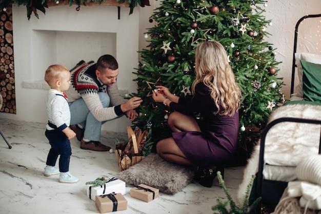 Piękna blondynka z mężem i uroczym dzieckiem siedzącym w pobliżu choinki, dekorując ją