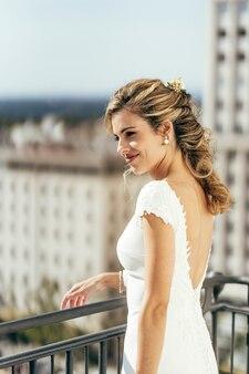 Piękna blondynka z włosami ubrana na biało w dniu ślubu przed ślubem.
