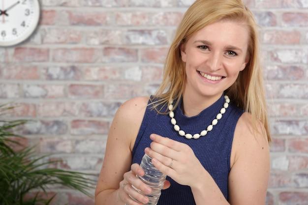 Piękna blondynki biznesowej kobiety woda pitna