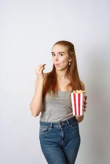 Piękna blondynki dziewczyna je popkorn i ogląda comedia film odizolowywającego na biel ścianie. skopiuj przestrzeń, szablon do blogu i reklamy. kobieta trzymać kukurydza pop