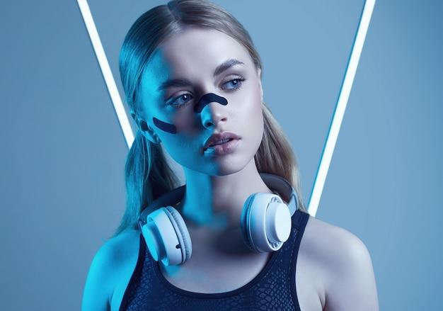 Piękna blondynki dziewczyna słucha muzykę w neonowych światłach z białymi hełmofonami
