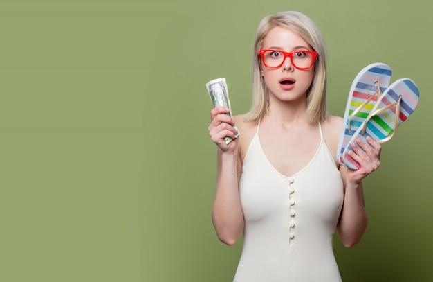 Piękna blondynki dziewczyna w szkłach z pieniądze i klapami