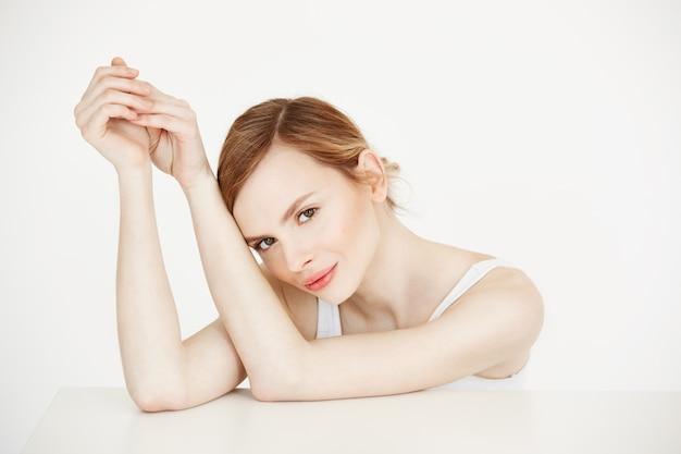 Piękna blondynki dziewczyna z perfect czystej skóry uśmiechniętym obsiadaniem przy stołem. kosmetyka. zabieg na twarz.