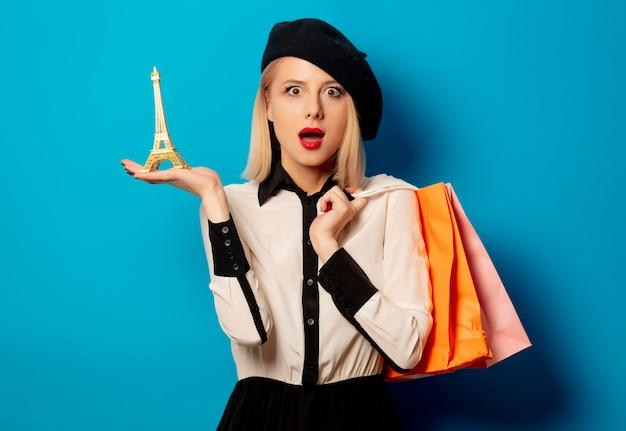 Piękna blondynki dziewczyna z torba na zakupy i wieżą eifla na błękit ścianie
