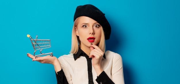 Piękna blondynki dziewczyna z wózek na zakupy na błękit ścianie