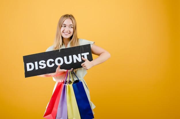 Piękna blondynki kobieta ono uśmiecha się i krzyczy z rabata znakiem i kolorowymi torba na zakupy odizolowywającymi nad kolorem żółtym