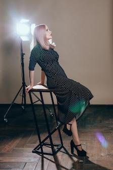 Piękna blondynki kobieta pozuje przy studiiem w świetle błyska. młoda ładna kobieta w czarnej sukni