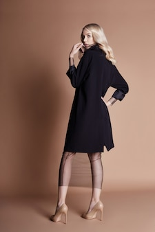 Piękna blondynki kobieta pozuje w czarnym żakiecie
