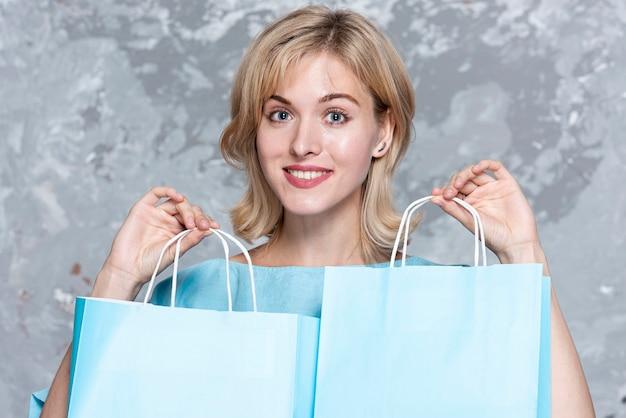 Piękna blondynki kobieta trzyma papierowe torby
