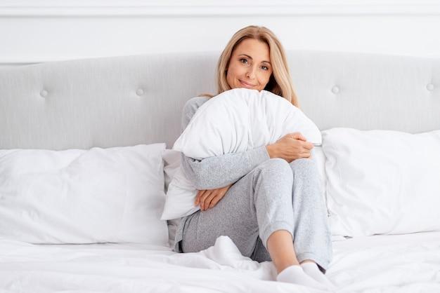 Piękna blondynki kobieta trzyma poduszkę