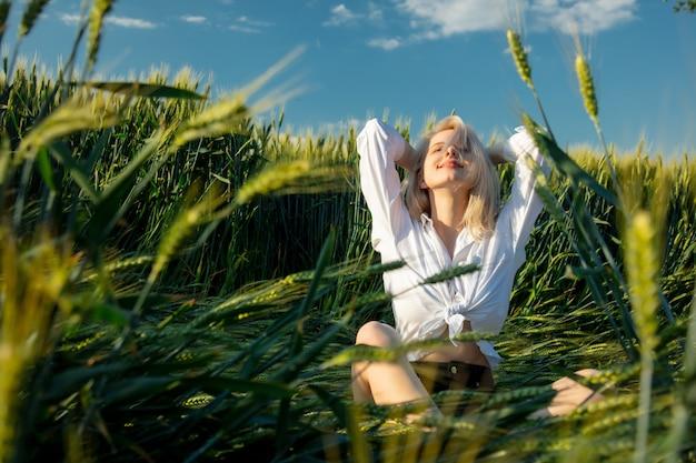 Piękna blondynki kobieta w białej koszula siedzi między pszenicznymi ucho w polu podczas zmierzchu