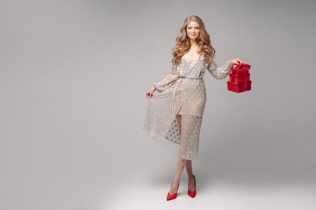 Piękna blondynki kobieta w eleganckiej sukni i szpilkach z stosem prezenty.