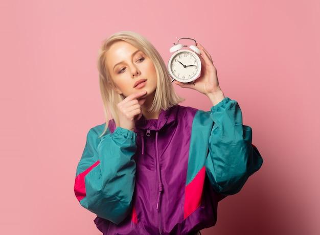 Piękna blondynki kobieta w latach 90. odziewa z budzikiem