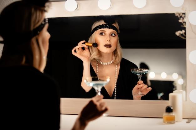 Piękna blondynki kobieta w latach dwudziestych ubraniach stosuje makijaż blisko lustra z żarówkami