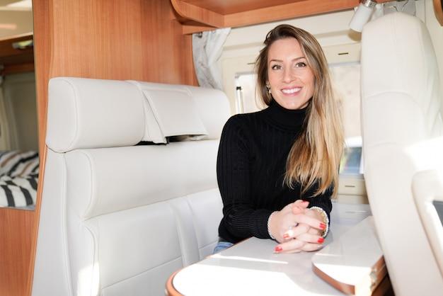 Piękna blondynki kobieta w motorowym obozowicza samochodu dostawczego domu rv w samochodu dostawczego życia uśmiechniętym szczęście sposobie życia vanlife