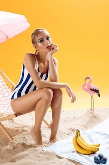 Piękna blondynki kobieta w pasiastym swimwear obsiadaniu na plażowym krześle