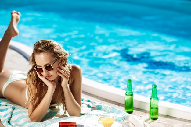 Piękna blondynki kobieta w sunbathing w swimwear, kłama blisko pływackiego basenu