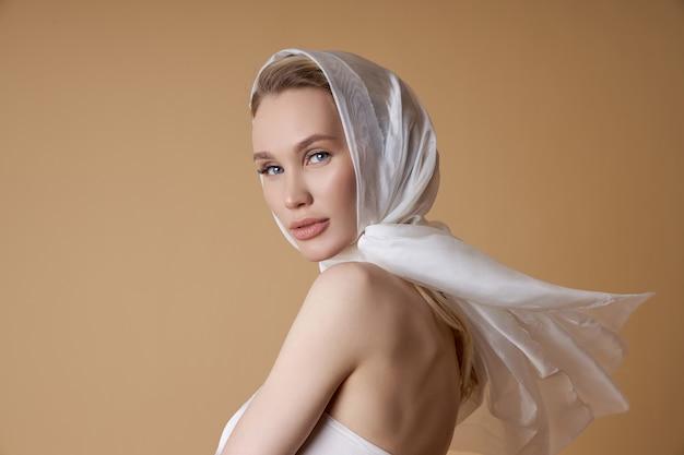 Piękna blondynki kobieta z dużym białym chustka na głowę