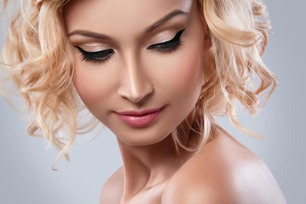 Piękna blondynki kobieta z eyeliner na ona oczy