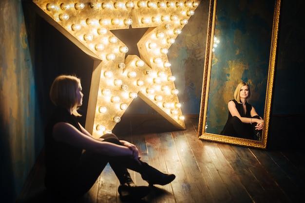 Piękna blondynki młoda kobieta w czarnym obsiadaniu na podłoga na tle gwiazdowe lampy i spojrzenie przy lustrem.