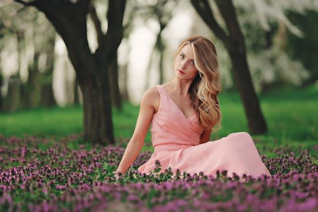 Piękna blondynki młoda kobieta w kolorowych kwiatach. dziewczyna z makijażem i fryzurą w różowej sukience w kwitnącym wiosennym parku. dzień kobiety