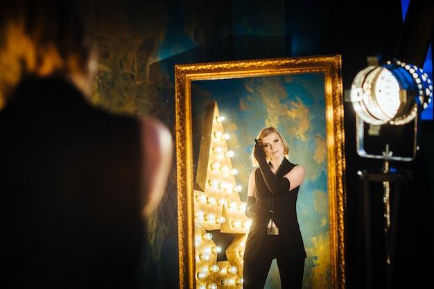 Piękna blondynki młoda kobieta zostaje w lustrze blisko gwiazdy z lampami w czerni ubraniach i rękawiczkach.