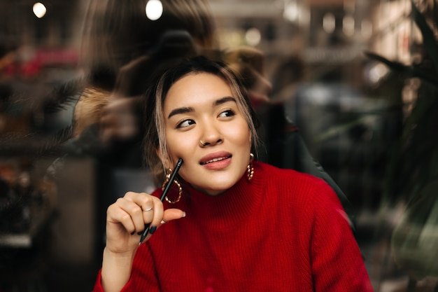 Piękna brązowooka kobieta w dużych złotych kolczykach i czerwonym stroju w zamyśleniu pozuje z piórem w dłoniach