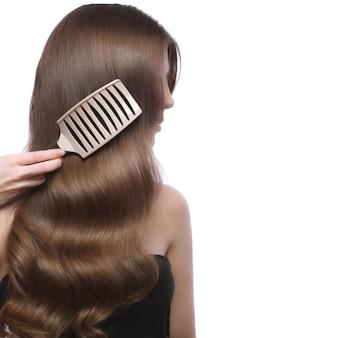 Piękna brązowowłosa dziewczyna o idealnie gładkich włosach i klasycznym makijażu.