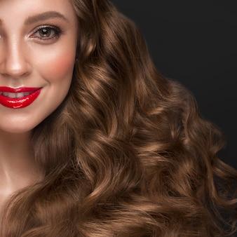 Piękna brązowowłosa dziewczyna o idealnie kręconych włosach, czerwonych ustach i klasycznym makijażu.